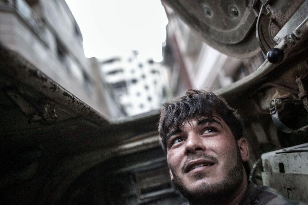 Militar das forças governamentais sírias em veículo blindado durante confrontos com militantes no centro da cidade de Homs