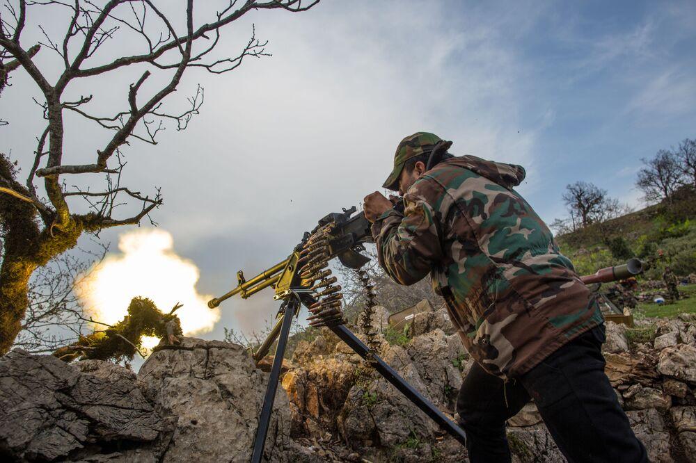 Soldado das forças governamentais sírias dispara metralhadora na cidade de Kesab