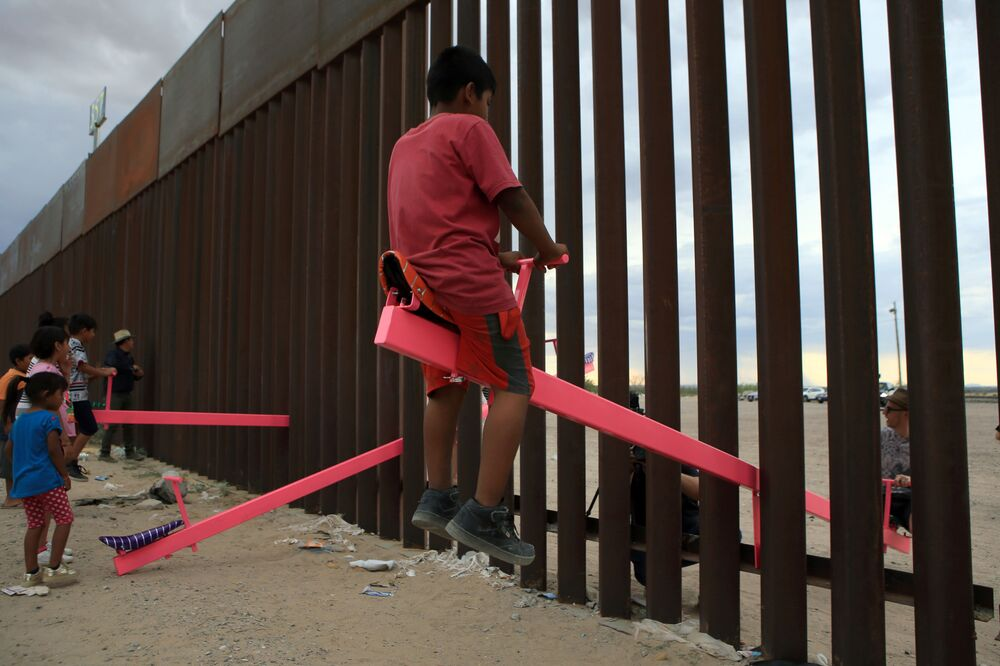 Famílias brincam na fronteira entre os EUA e o México na região de Anapra