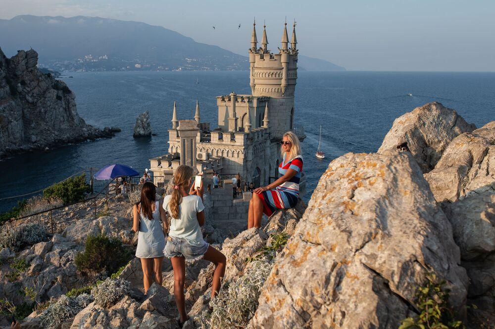 Turistas tiram fotos em frente ao castelo Ninho da Andorinha na Crimeia, Rússia
