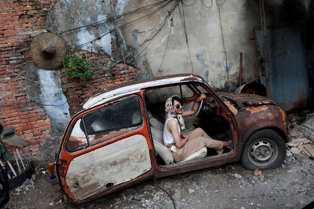 Menina tira foto em um carro antigo em área turística de Bangkok, na Tailândia
