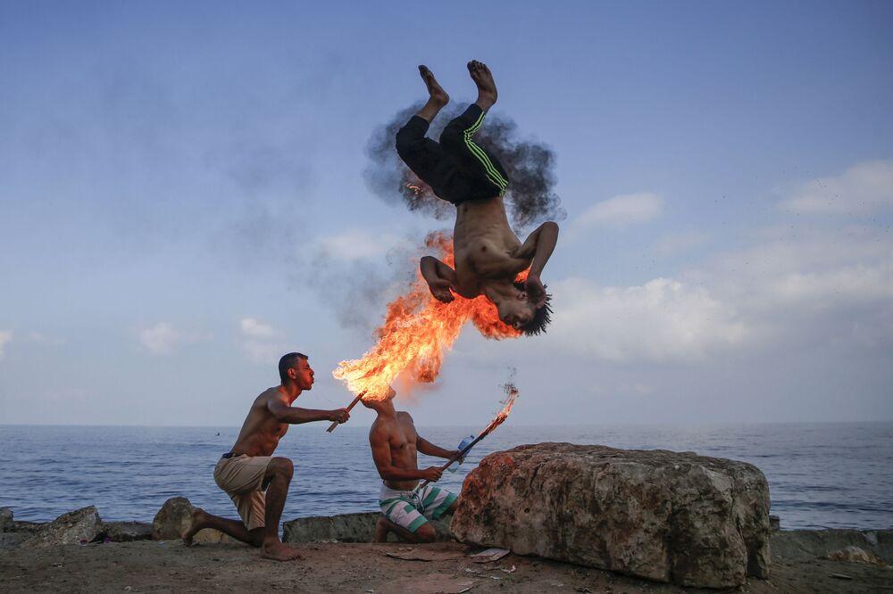 Faquires palestinos atuam durante férias de verão em Gaza