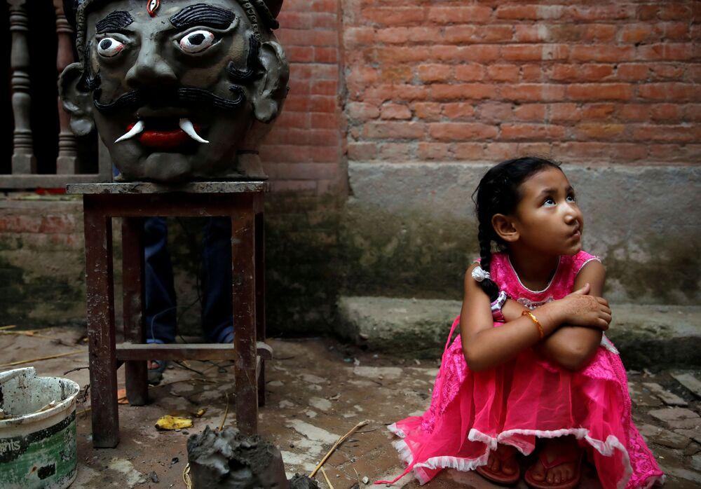 Garota sentada ao lado de cabeça de demônio no Nepal