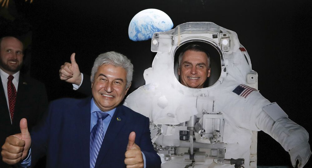 O presidente do Brasil, Jair Bolsonaro (PSL), posa para uma foto atrás de um modelo de astronauta dos EUA. Ao seu lado está o ministro da Ciência e Tecnologia, Marcos Pontes. A foto foi tirada em um evento na embaixada dos Estados Unidos em comemoração à independência do país no dia 4 de julho de 2019.