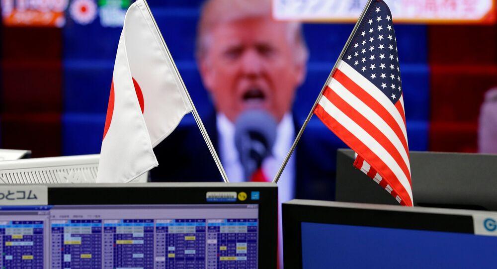 Bandeiras dos EUA e do Japão em frente de monitor com o presidente Donald Trump