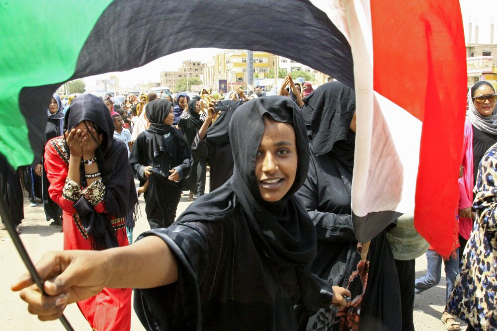 Uma jovem sudanesa com a bandeira nacional durante a celebração da assinatura do Acordo Constitucional entre o Conselho de Guerra e a Frente Nacional de Libertação do país sobre o estabelecimento de um governo de transição
