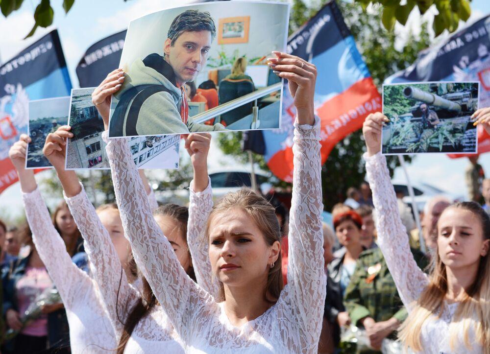 Participantes da cerimônia de homenagem no lugar onde morreu Andrei Stenin, fotojornalista da agência de notícias Rossiya Segodnya