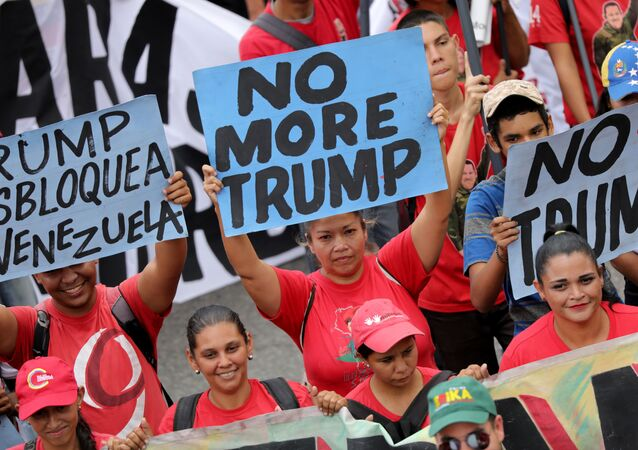 Apoiadores do governo da Venezuela durante manifestação com cartazes contra o presidente dos EUA Donald Trump em Caracas, na Venezuela