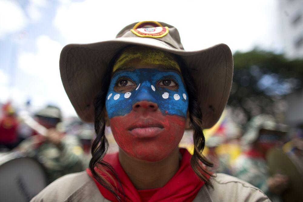 Moça com a cara pintada de cores da bandeira nacional durante a manifestação contra as sanções aplicadas pelos EUA, em Caracas