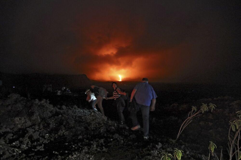 Pessoas sobem uma encosta para observar a erupção do vulcão Piton de la Fournaise na parte oriental da ilha de Reunião, no oceano Índico, 13 de agosto de 2019