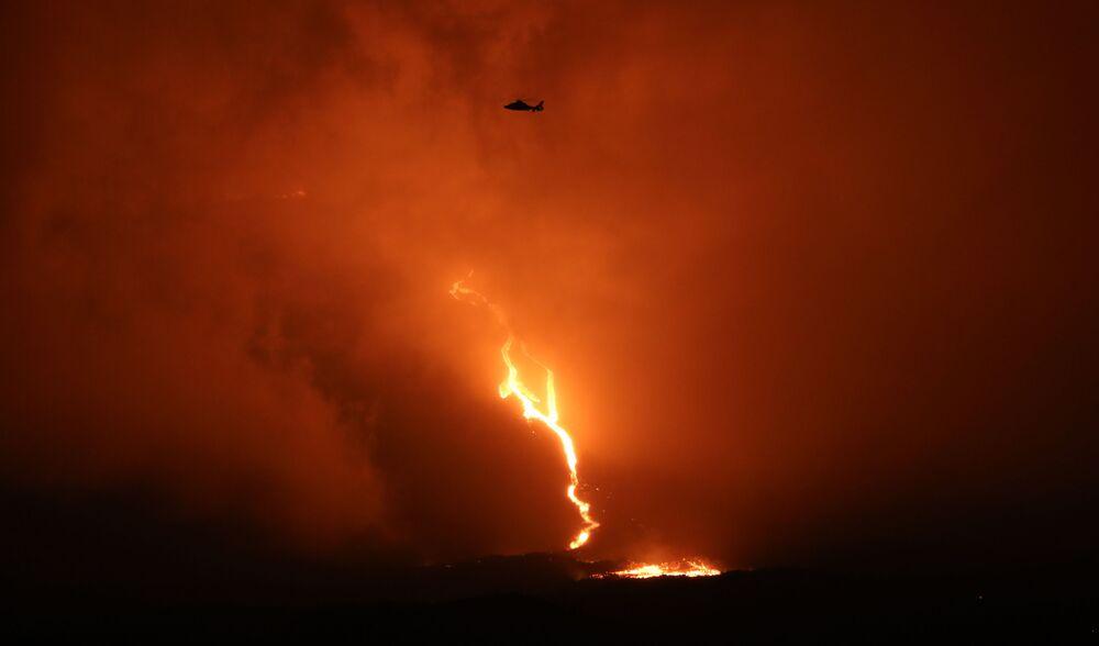 Helicóptero sobrevoa o vulcão Piton de la Fournaise, enquanto a lava desce pela encosta este-sudeste, na ilha de Reunião, no oceano Índico, 13 de agosto de 2019