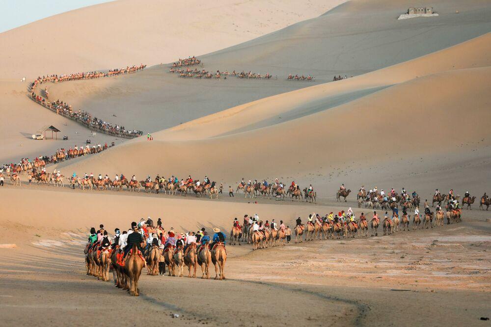 Turistas em camelos no deserto nos arredores da cidade de Dunhuang, noroeste na China