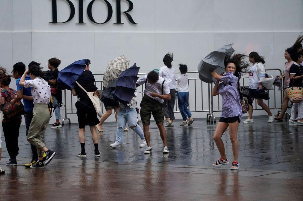 Pessoas nas ruas de Xangai durante a aproximação do tufão Lekima
