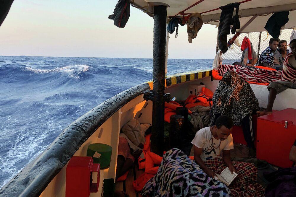 Imigrante lê o Corão a bordo do navio dos socorristas espanhóis Open Arms no mar Mediterrâneo
