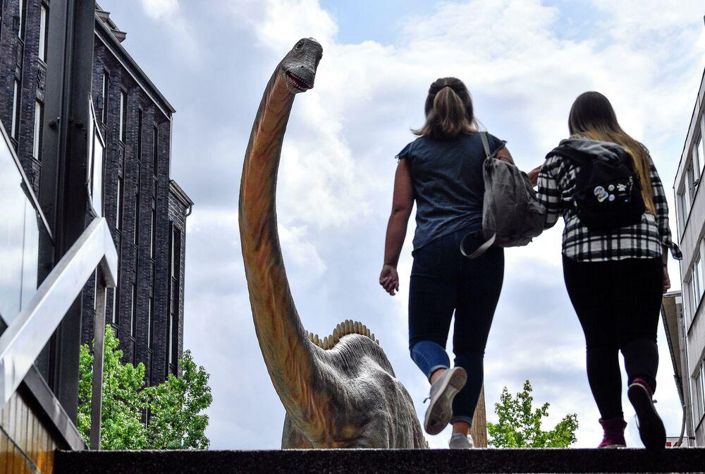 Mulheres passando ao lado de réplica de tamanho real do dinossauro Diplodoco no centro da cidade de Bochum, Alemanha