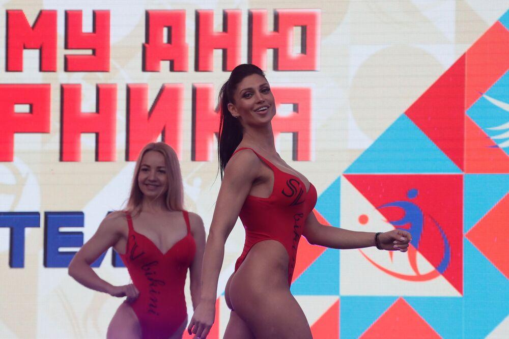 Mulheres posando no palco durante as celebrações do Dia do Esportista em Moscou