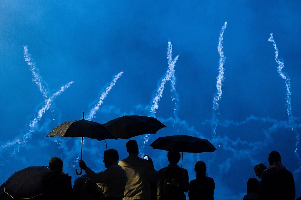 Pessoas com guarda-chuvas observam o Festival Internacional de Fogos de Artifício Rostec em Moscou, 17 de agosto de 2019