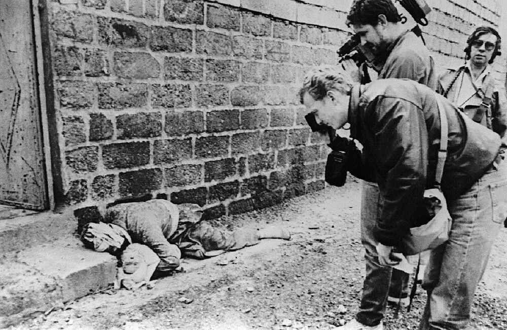 Fotógrafo e operador de câmera registram um curdo segurando um bebê, ambos mortos, em uma rua de Halabja, no nordeste do Iraque, em 20 de março de 1988