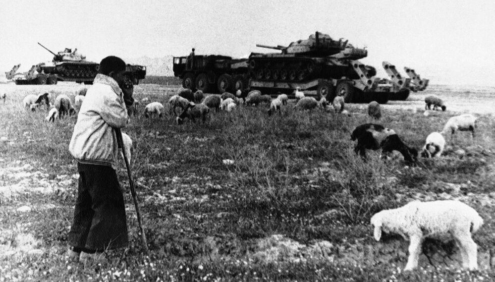 Um jovem pastor observa caminhões transportando tanques perto da cidade de Ahvaz, no sul do Irã, devastada pela guerra, em 17 de abril de 1981
