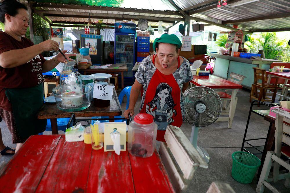 Vendedor de rua observa cobra capturada em garrafa de plástico