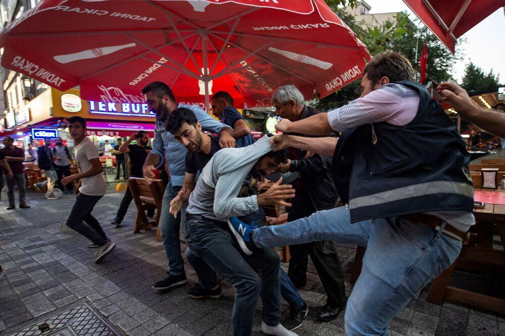 Um policial detém um participante do protesto em Istambul contra a substituição dos prefeitos curdos por funcionários do governo turco