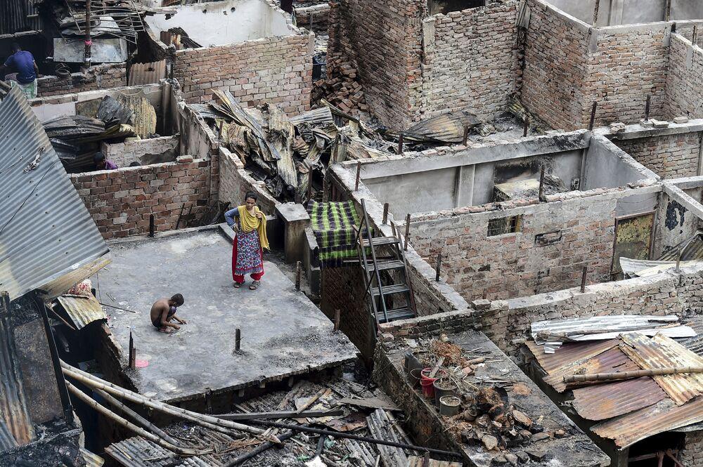 Criança brinca no telhado de uma casa destruída pelo fogo em uma favela de Daca, capital do Bangladesh
