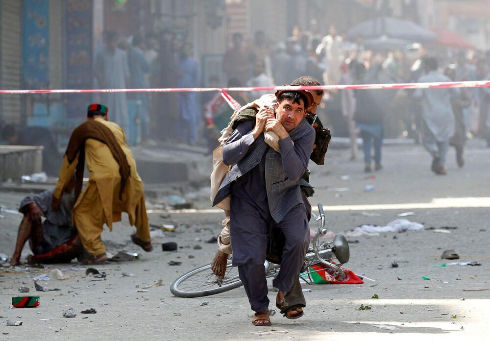 Homem leva um ferido para o hospital após a explosão em Jalalabad, no Afeganistão