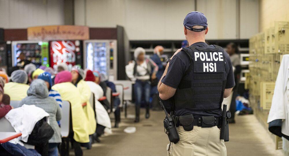 Oficial do serviço de imigração observa imigrantes ilegais detidos