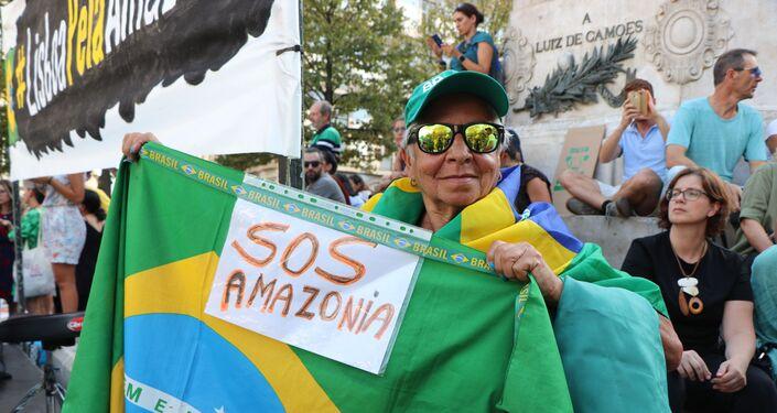 Manifestante com a bandeira do Brasil e cartaz SOS Amazônia durante ato contra queimadas na Amazônia em Lisboa, Portugal em 26 de agosto de 2019
