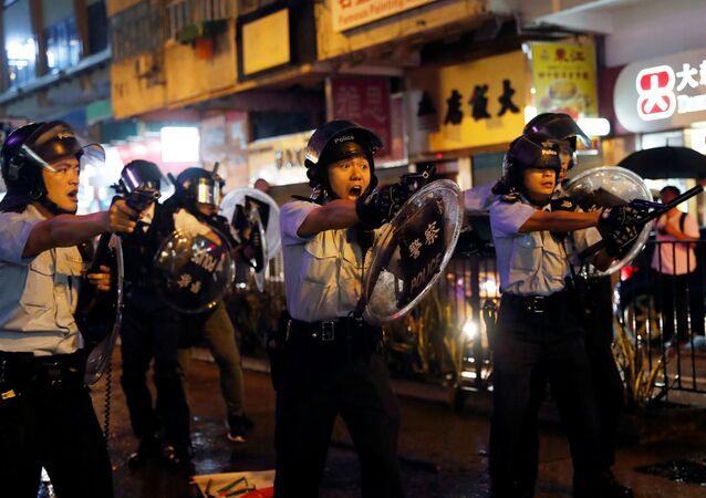 Policiais apontam armas para manifestantes contra lei de extradição após embates em Tsuen Wan, em Hong Kong