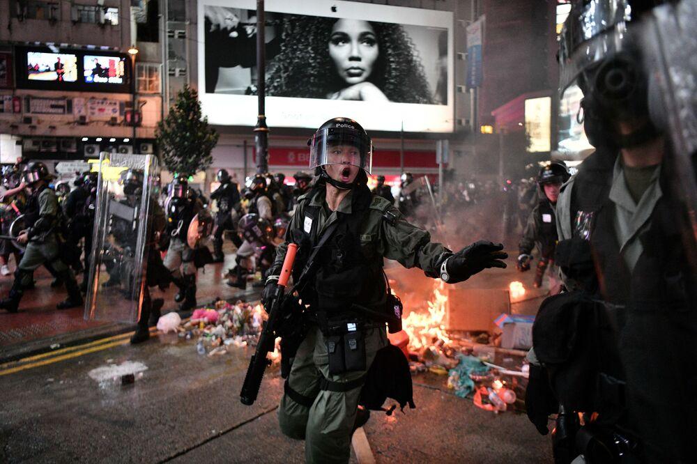 Polícia passa por destroços incendiados por manifestantes ao longo de uma rua em Hong Kong