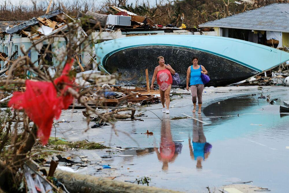 Mulheres andam entre destroços deixados pelo furacão Dorian em uma das ilhas das Bahamas
