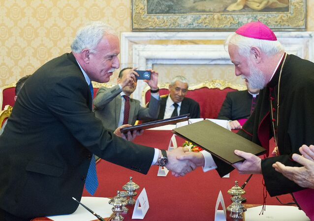 Vatican Foreign Minister Paul Gallagher, right, and his Palestinian counterpart, Riad al-Malki, shake hands after signing a treaty at a ceremony inside the Vatican, Friday, June 26, 2015.