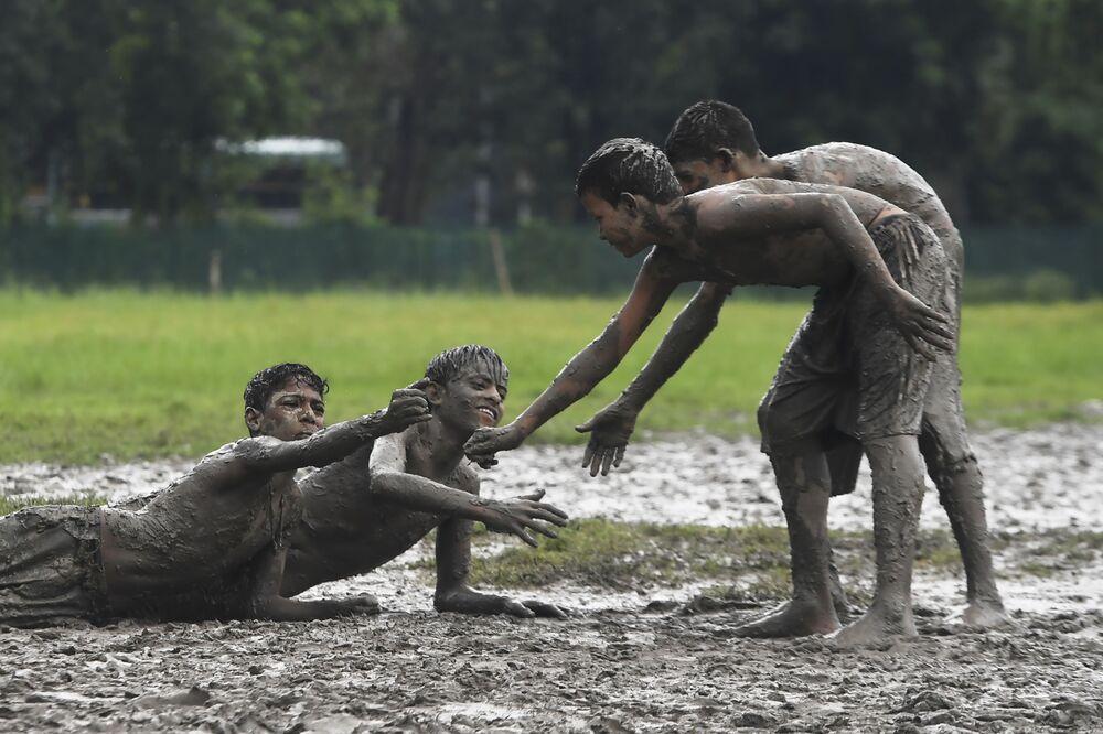 Crianças brincam em áreas alagadiças de Calcutá