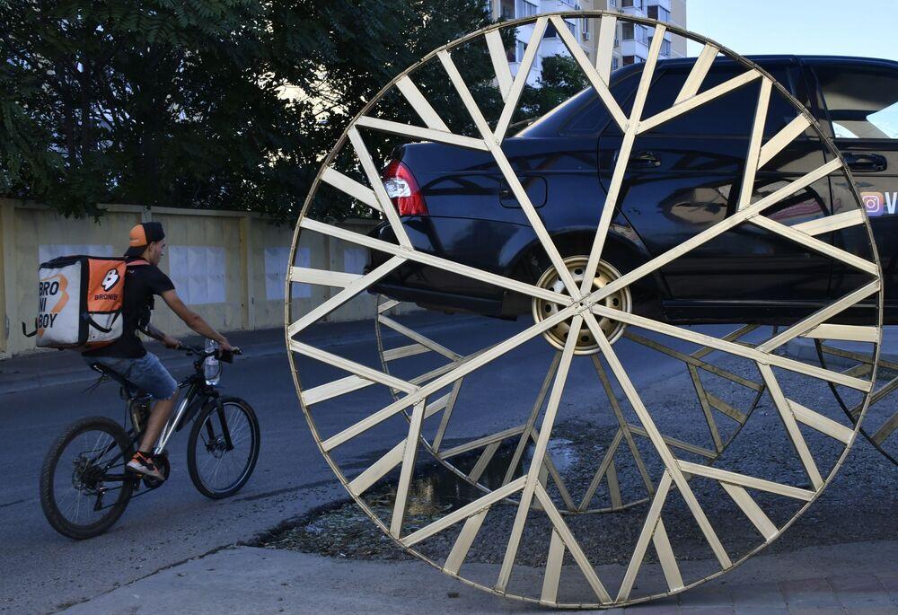 Carro LADA Priora com rodas de 2 metros de diâmetro em uma rua da cidade russa de Krasnodar