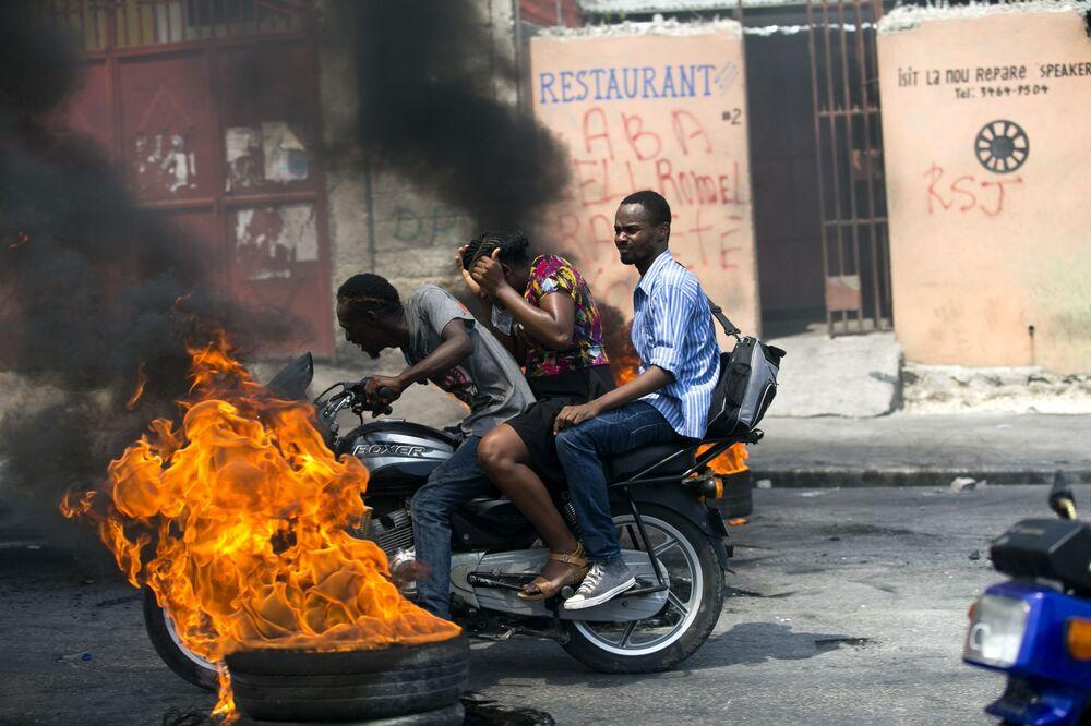 Mototáxi passando por pneu em chamas em Porto Príncipe, no Haiti, 16 de setembro de 2019