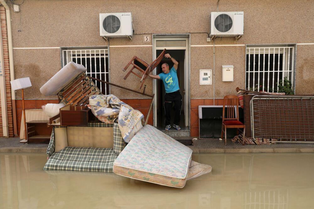 Homem joga fora móveis danificados pelas chuvas fortes, em Almoradi, na Espanha, em 17 de setembro de 2019