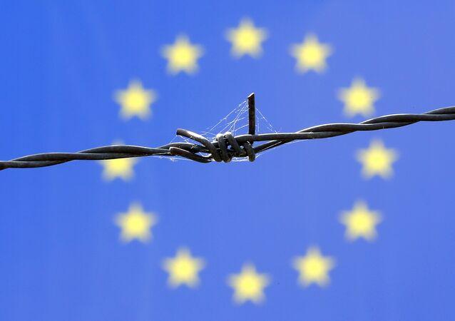 Arame farpado em frente à bandeira da União Europeia.