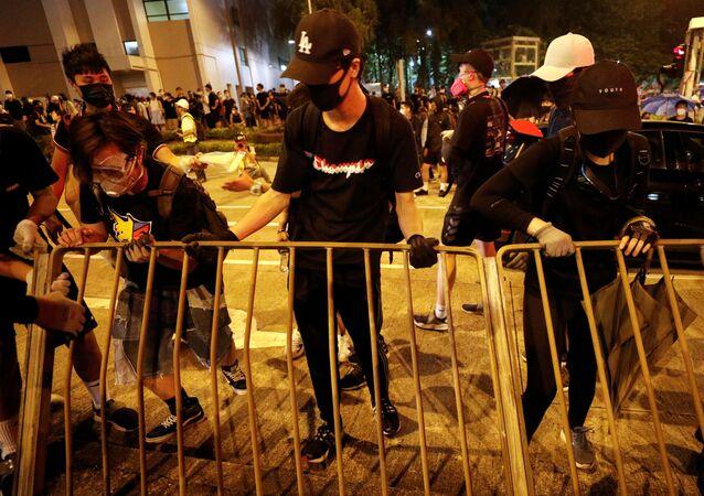 Manifestantes retiram uma grade do lado e fora do estádio Rainha Elizabeth, em Hong Kong, onde a chefe-executiva da região, Carrie Lam, realiza diálogos com membros das manifestações.