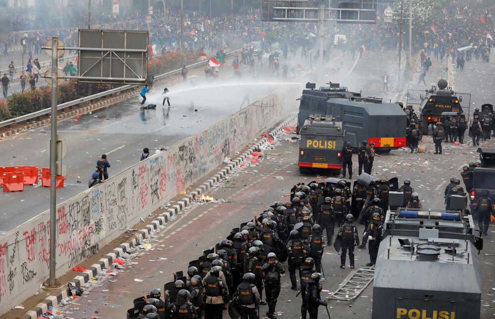 Polícia antimotim indonésia usa canhão de água contra manifestantes universitários próximo ao parlamento do país na capital Jacarta, em 24 de setembro de 2019