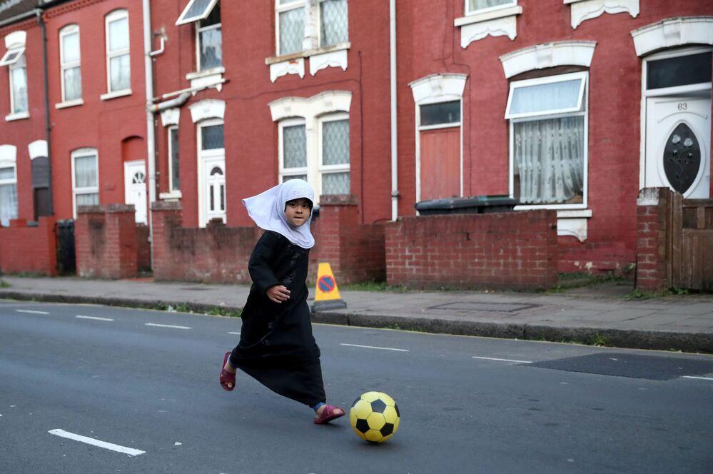 Criança jogando futebol em uma das ruas de Luton, Reino Unido