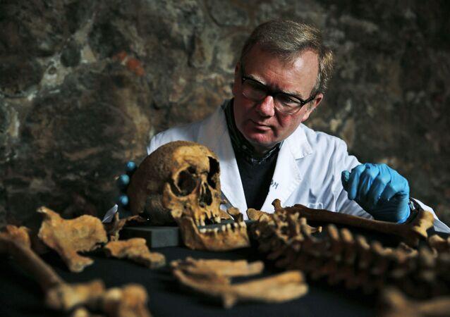 Cientista observa esqueleto de vítima da Peste Negra na Grã Bretanha (foto de arquivo)