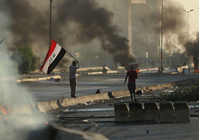 Manifestantes contra o governo no Iraque ateiam fogo em objetos para fechar via em Bagdá no dia 5 de outubro de 2019.