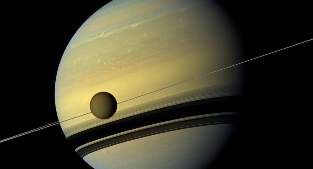 Maior lua de Saturno, Titã, passando em frente ao planeta gigante em imagem feita pela nave espacial Cassini da NASA