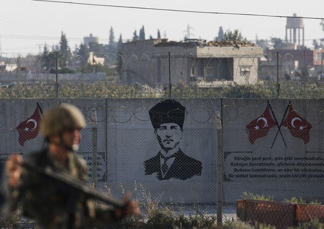 Soldado turco posicionado na fronteira com a Síria em frente ao grafite do Mustafa Kemal Ataturk, fundador da da República da Turquia