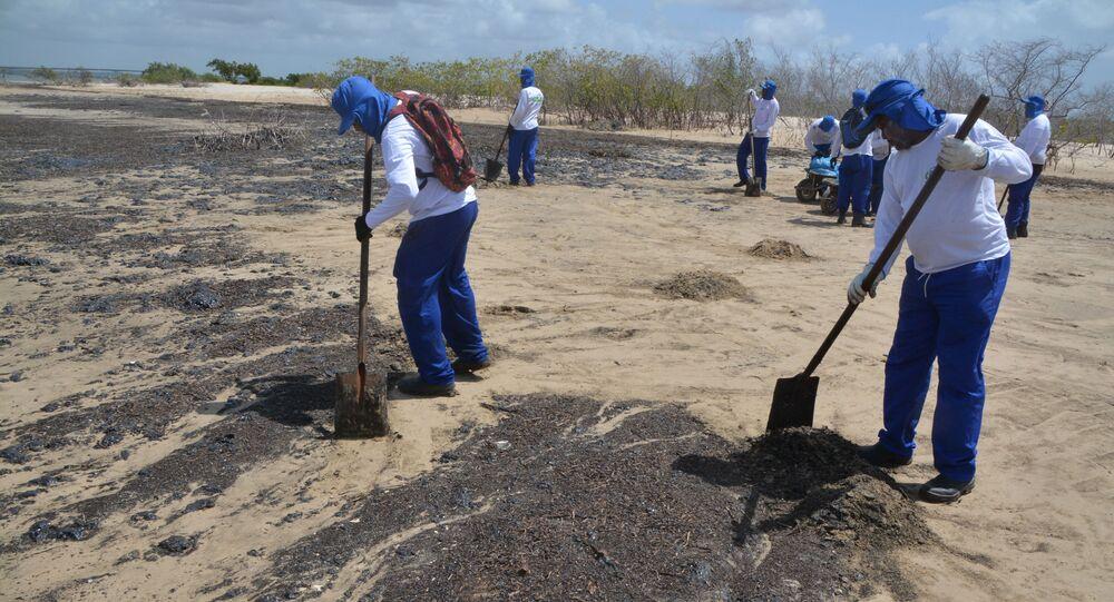 Agentes limpam manchas de óleo que atingiram a praia do Viral, na região de Mosqueiro, em Aracaju (SE)