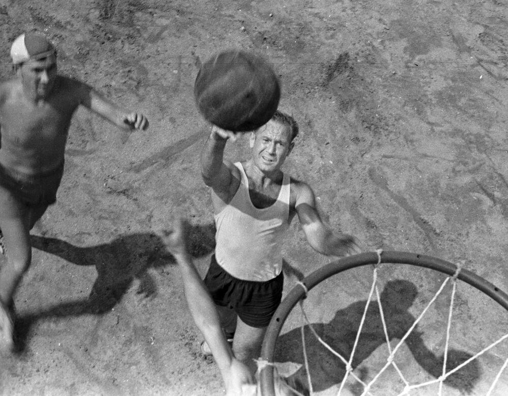 Lendário cosmonauta atira bola de basquete na cesta.