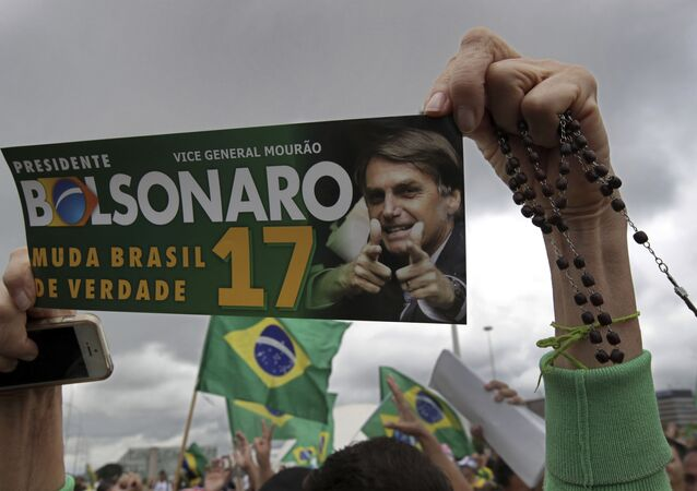 Apoiadora do então candidato à Presidência da República do Brasil, Jair Bolsonaro (PSL), segura terço e uma foto do candidato, Brasília, 21 de outubro de 2018