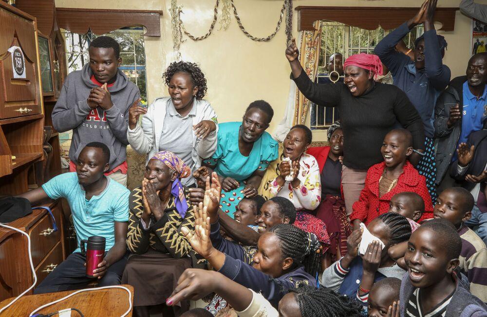 Mãe, amigos e vizinhos do corredor queniano Eliud Kipchoge assistem à maratona durante a qual o atleta estabeleceu um novo recorde mundial