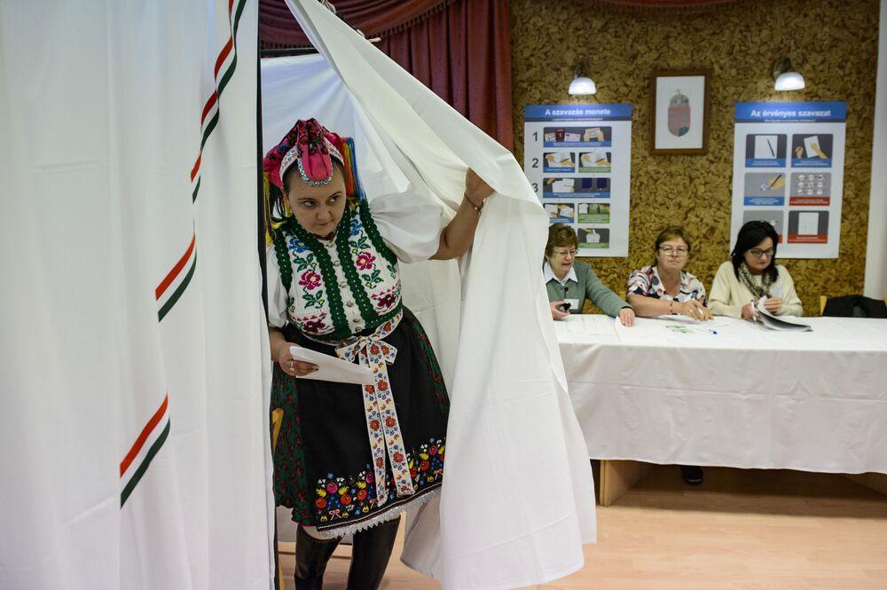 Mulher em roupa tradicional sai da cabine de votação durante eleições locais no povoado de Rimoc, Hungria